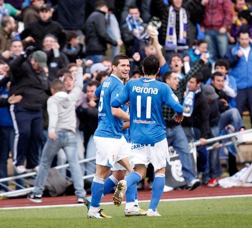 Los oviedistas celebran el gol ante la enfervorecida afición azul congregada en La Maruca (Foto: Jonás Sánchez).