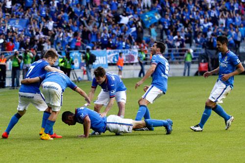 Los azules corren a abrazar a Cervero, que celebra su gol haciendo planchas (Foto: José Luis González).